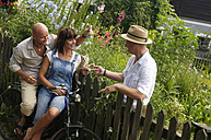 Couple sitting on bicycle talking with neighbor - HHF00886