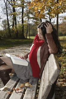 Young woman sitting on bench, reading book - LDF00411