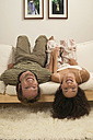 Young couple lying headfirst on sofa - WESTF03708