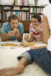 Three young people lying on floor, eating pizza - WESTF03702