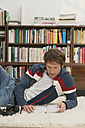Young man lying on floor, reading - WESTF03684