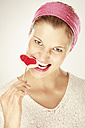 Young woman eating heart shaped lollipop, close-up, portrait - LDF00444