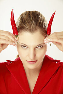 Young woman holding chili on head, simulating horns, portrait - LDF00435
