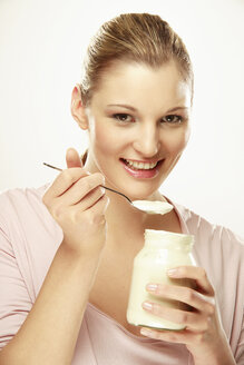 Young woman eating yoghurt, portrait - LDF00432