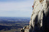 Germany, Bavaria, two people climbing on rock face - FFF00745