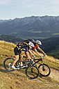 Austria, Tirol, couple riding bicycle - FFF00717