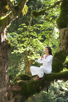 Young woman meditating on tree branch, side view - HHF01152