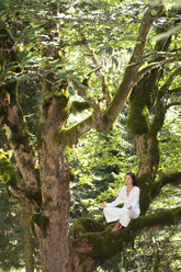 Young woman meditating on tree branch, side view - HHF01149
