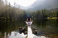 Woman exercising yoga at lake, rear view - HHF01146