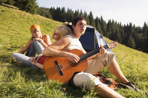 Young people in meadow, man playing guitar, tilt view - WESTF04326