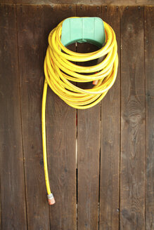 Yellow hosepipe hanging on brown wooden wall - PM00495