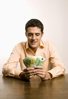 Young man holding diverified Euro banknotes - LDF00465