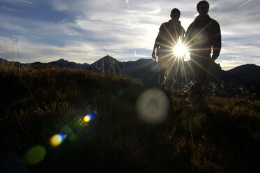 Couple standing in mountains in backlight - WESTF04262