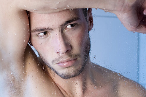 Young man under shower behind glass pane, close-up - MAEF00152