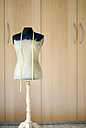 Mannequin and tape measure in front of wardrobe - NHF00378