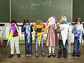 Children (4-7) standing in front of blackboard looking in to school cones - WESTF04594