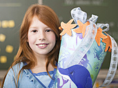 Girl (6-7) holding school cone, smiling, portrait, close-up - WESTF04493