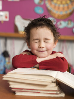 Boy (4-5) sitting at desk and leaning on stack of books, eyes closed, close-up - WESTF04460