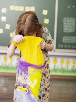 Girl (6-7) looking into school cone - WESTF04457