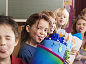 Children (4-7) holding school cone, sticking out tongue - WESTF04442