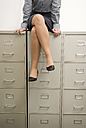 Businesswoman sitting on filing cabinet, low section - WESTF04840
