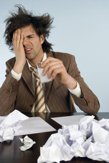 Businessman sitting on desk with head in hands, papers around - WESTF04822