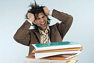 Man sitting at desk with piled files, shouting - WESTF04813