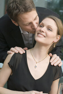 Man kissing woman's cheek - NHF00533