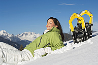 Woman with snowshoes, relaxing - HHF01372