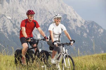 Couple cycling across a meadow - MRF00889