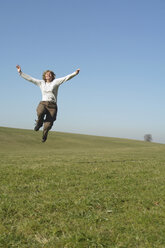 Woman jumping in meadow, arms up - GNF00916