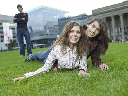 Germany,Stuttgart, young women lying in meadow, young man watching in background - KMF00974