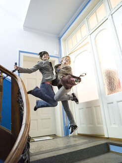 Two girls jumping on staircase - KMF00938