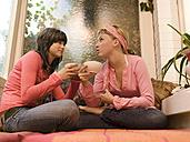 Girl friends sitting on sofa, drinking tea - KMF00932