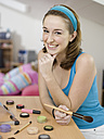 Young woman holding cosmetic brush, portrait - KMF00917