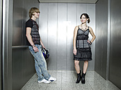 Young couple standing in lift - KMF00893
