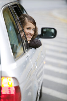 Young woman looking out of car, smiling - KMF00851