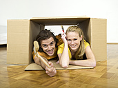 Couple lying in box, holding brushes - WESTF05192