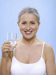 Senior woman holding glass of water, portrait - WESTF05355