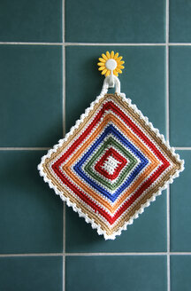 Pot holder hanging on tiled wall, close-up - TLF00099