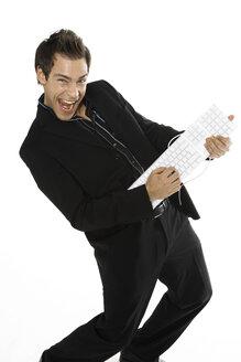 Young man holding keyboard, close-up - PKF00174
