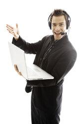 Young man wearing headphones, holding laptop,close-up - PKF00138