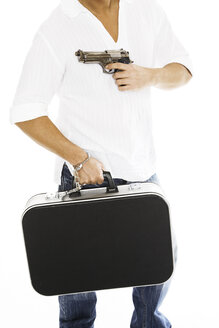 Man carrying money case, aiming with pistol, close-up - PKF00114