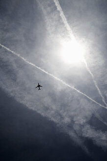 Condensation trails and airplane in sky - TLF00180
