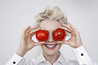 Young woman holding tomatoes in front of her eyes, portrait - TCF00210