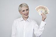 Young woman holding money, portrait - TCF00180