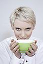 Young woman holding tea bowl, portrait - TCF00168
