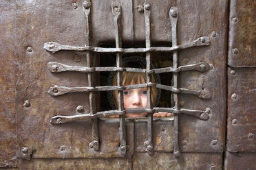 Italy, South Tyrol, Potrait of a girl behind bars - GNF00939