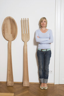 Young woman standing beside giant cutlery - NH00634