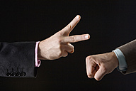 Businessmen playing rock paper scissors, close-up of hands - CLF00465